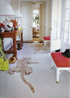 I like how the furniture is so classic and then there's leopard shaped rugs on the floor.  Love that touch.    Climbing leopard rug by Diane Von Furstenburg playfully used in hallway by Jeffrey Bilhuber.