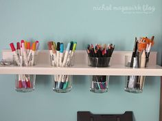 Wall-mounted shelf with holes... drop in glass cups + use to store pens/pencils/things in