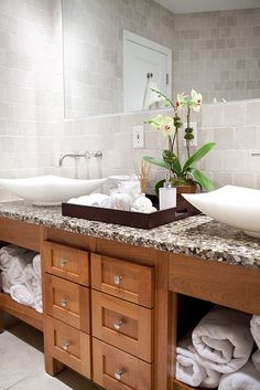Oak bathroom cabinets double sinks white stone vessel sinks brushed nickel wall-mount faucets corian countertops.