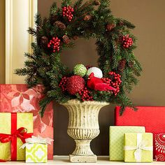 Festive Holiday Urn. Turn a garden urn into a Christmas decoration. Adorn the arrangement with berries, pinecones, and sparkling orbs. Add symmetry with neatly wrapped presents.