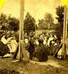 A crowd gathers round to watch a young boy push a woman on a swing, in this unique, delightful Victorian slice-of-life snapshot. #Victorian #crowd #1800s #swing #outdoors