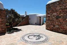"""This classic house in Mikonos, Greece gives this picturesque hotspot a run for its money. Designed by Catalan architect Javier Barba of architecture firm BC Estudio, the house evokes the traditional architectural style of the island, with characteristic elements like domes, rounded walls and a whitewashed facade combined with stone walls that help to """"ground"""" the classic yet modern design."""