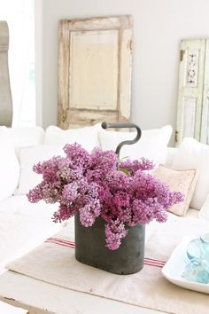 Beautiful purple lilacs in white sitting room.