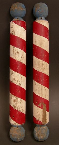 """Pair of painted wooden barber poles in their original first paint. These bulbous turned poles are flat on the back and hung on the outside of the barber shop on each side of the front door. They measure 48"""" tall. They are very bold and all original, circa 1890-1900."""