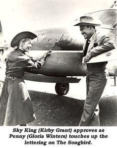 Sky King (Kirby Grant) approves as Penny (Gloria Winters) touches up the lettering on The Songbird.