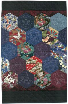 """Hexagon-Sashiko Quilt."" Crane and flower motifs combine with geometric hexagons in this quilt. To make this arrangement of hexagons appear more oriental, dark indigo bands were added to the top and bottom."