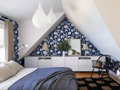 It might seem counterintuitive to cover a small room's walls with a dark pattern, but a moody paper actually accentuates this snug space's comfy vibe.