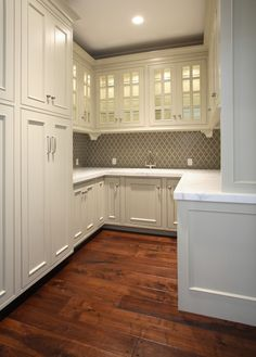 Love. Love. Love. Gorgeous butler's pantry with ivory glass-front kitchen cabinets with marble countertops , Gray Ann Sacks Moorish Tiles backsplash and polished nickel bridge faucet.