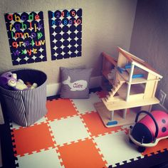 "Cute space using SoftTiles 1x1 foam mats. http://www.softtiles.com/index.php?option=com_virtuemart&Itemid=113  ""Living room play area complete!  Plan toys doll house from a garage sale. Orange & white foam mats from soft tiles. DIY magnet boards. Striped fabric toy bin from home goods."""