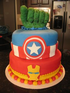 The Avengers Cake - The Avengers Cake Hulk fist made from rice krispie treats covered in modeling chocolate, details painted in food coloring. Iron Man and Captain America details in fondant. www.thecrumbcoat.wordpress.com