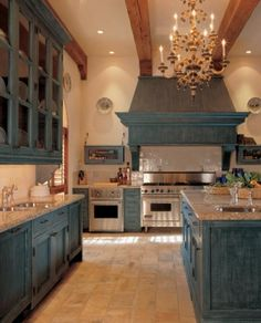 I like the color of these cabinets.Blue-gray—with warm, even distressed finishes. But in contemporary homes with streamlined cabinetry, I go much bolder. I just did one with red lacquered cabinets, stainless hardware and black countertops.    Bunny Williams