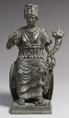 Statuette of a Personification of a City, 300–500 Late Roman or Byzantine. Tyche, the personification of chance or fortune, was also understood as the protector of cities. Here, Tyche sits on a low throne. Wearing a mural crown, chiton, and peplos, she holds a cornucopia in her left hand. She extends her right hand, which held a now-missing attribute, possibly a staff. It is difficult to identify which city is represented by the statuette.