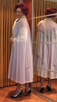Prim plastic overdress, with white cape worn over