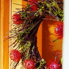 This wreath using manzanita, Spanish moss, canella berries, and proteas combines woodsiness with exoticism.