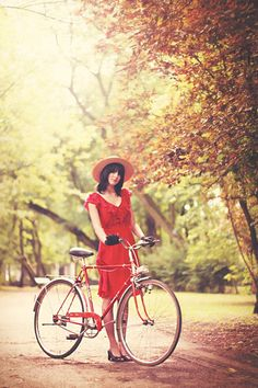 sun hat, red dress, and bicycling in the park.