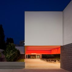 Narrow skylights create bands of light across the red bright ceiling of a sheltered school courtyard