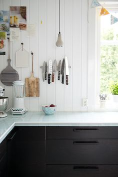 hanging light cutting boards from hooks on the wall, pale teal glass tile countertops, black lower cabinets