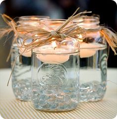 Beautiful Mason Jar centerpieces with floating candles and raffia