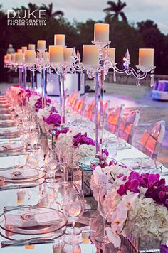 Tall, crystal candelabras glow above white hydrangeas and phalaenopsis orchids in square vessels below.