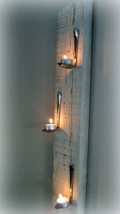 Board with bent spoons holding tealights