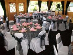 White chair covers and tablecloth, with organza sashes, overlays and pink napkins.