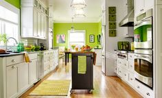 Updated white cabinets, lime green walls, and a streamlined layout make for a cookspace that's roomy and bright, no matter how many cooks are in the kitchen. Shop this room! Check out the This Old House Shop on @wayfair