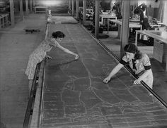 Women marking the pattern of uniforms onto material with chalk in preparation for the cutting stage of the process. Nine hundred miles of khaki serge produces 5,000,000 battle suits and 6,000,000 pairs of trousers. UK, 1941.