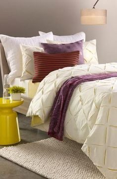 Neutral bedroom with hues of deep red, lavender, & yellow.