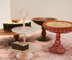 This creative presentation showcases various treats and cake stands on top of a rosette tablecloth.