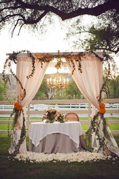 Rustic Wedding Reception - Chandelier and Curtains around the Sweetheart Table for the Bride and Groom