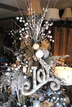lots of different sizes, textures in topper.  Use the covered styrofoam balls, burlap and plaid ribbon. Use various styles of twigs for height.