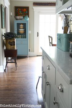 Love the vintage blue medical cabinet in this beautiful white kitchen eclecticalyvintage.com #EclecticallyFall