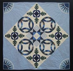 Ann Quilts:  A Wedding Quilt.  Double Wedding Rings, oak leaves and Ohio star. In the corners are four sunbursts from a New York Beauty block.