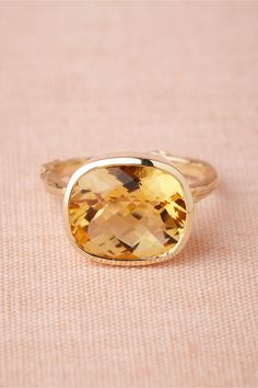 Pooling Citrine Ring $450.00$980.00   WRITE A REVIEW STYLE: 27031277  A checkered cushion-cut of citrine wrapped in smooth gold rests regally on a slim twig band. By Alex Monroe. 9k yellow gold, 12mm citrine. Handmade in UK.