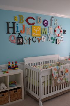 Alphabet in different colors & fonts on wall above crib makes this gender neutral nursery  pop!