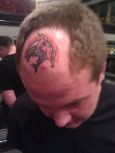 Unicorn making love to dolphin tattoo on forehead.