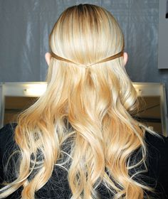 The Y Knot Apply a dime-size amount of volumizing mousse to roots of damp hair; comb through and let air-dry. Create loose low-lying waves holding a 1½-inch curling iron vertically and curling in alternate directions; polish with a hydrating cream. For the Y, make an anchor—a small braid on the underlayers of hair, near the nape—then join two thin strands from each side in the back with an elastic before U-pinning them to the hidden braid.