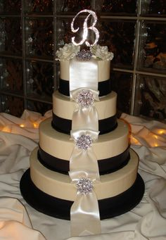 Candlelight buttercream iced wedding cake, with wide fondant ribbons and pearlescent bow loops cascading from the top tier to the bottom.