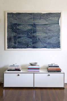 Bohemian Vintage Decor: An indigo textile framed and hung above a contemporary storage unit.