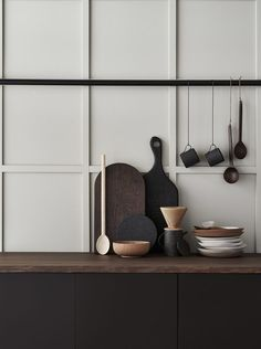 Matt layered kitchen utensils in earthy shades.