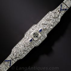 Art Deco Diamond and Sapphire Bracelet. A breathtaking Art Deco adornment - circa 1920s - masterfully hand-crafted in platinum with the utmost care and quality materials. With a bright-white and beautiful one carat square step-cut diamond as its centerpiece, this exquisite bracelet has a lovely stylized geometric leaf design that elegantly tapers as it encircles the wrist. With 7 carats of bright and sparkling accent diamonds and  French-cut sapphires adding an additional grace note