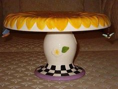 Sunflower cake plate pedestal with a hanging bumble bee and butterfly.