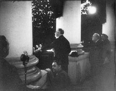 Roosevelt addresses the crowd at the Christmas tree lighting ceremony from the White House South Portico on December 24, 1941. Churchill can be seen on the right. (FDR Presidential Library)