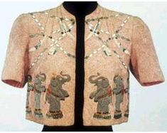 Schiaparelli Bolero jacket, 1938, dancing elephants Bolero jacket. embroideries of dancing circus elephants and swinging trapeze artists against a background of densely applied rose soutache. Part of her circus inspired designs.(AP Photo/Union des Arts Decoratifs)