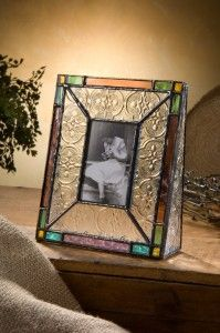"Always complementary, never overpowering.  Combining popular textured glass with shades of rose, sage, and light amber cathedral glass, they showcase precious memories with class. To bring even more light through the small 2"" x 3"" frame, the glass extends back from the sides. Shown here in the smallest size, this elegant vintage-looking photo frame is available in many sizes and styles up to 8"" x 10""."