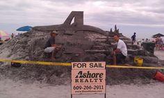 Master sand sculptor Matt Deibert and assistant Dennis Allen working on the Ashore Realty logo ....