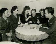 "Jane Withers with soldiers sitting at the ""Angel's Table"" at the Hollywood Canteen"