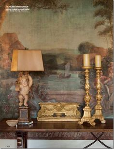 A vignette with a painted mural, water gilded candlesticks and a putti lamp.