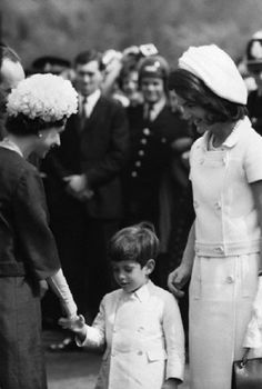 Queen Elizabeth II shakes hands with John Kennedy Jr, as he stands beside his mother Jackie at a memorial service for his father, at Runnymede, 1965.