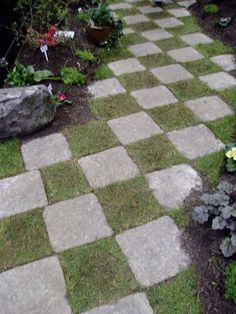Checkerboard pavers with grass or herbs in empty spaces. So creative and fun for outdoor space!